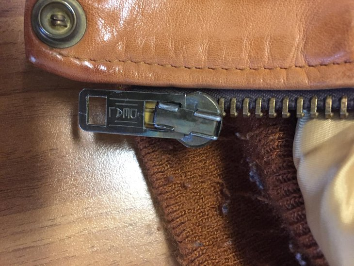 Zipper on a brown leather jacket.