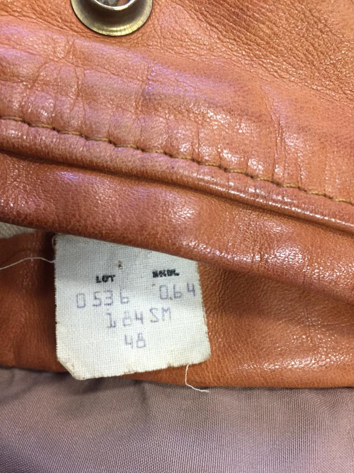 Production tag inside a brown lather jacket.